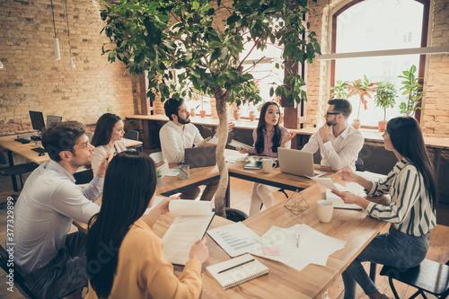 Photo of business men ladies people partners sitting around table desktop spacio Fototapeta