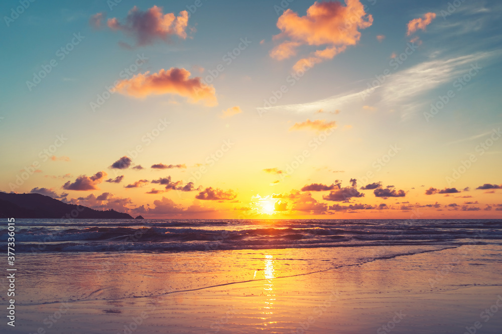 Fototapeta Tropical beach with smooth wave and sunset sky abstract background.