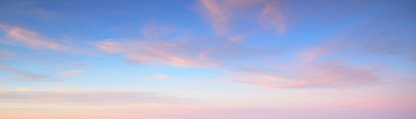 Clear blue sky with glowing pink cirrus and cumulus clouds after storm at sunset. Dramatic cloudscape. Concept art, meteorology, heaven, hope, peace, graphic resources, picturesque panoramic scenery