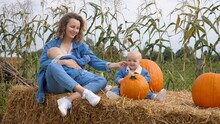 Young Mother Breastfeeding Her One Baby, Another One Is Sitting Right Next To Them On A Hay Bale In The Pumpkin Patch. Happy Childhoon Of Twins