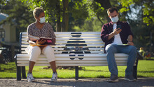 Two Students Wearing Masks Sitting On Bench Keeping Social Distance And Studying