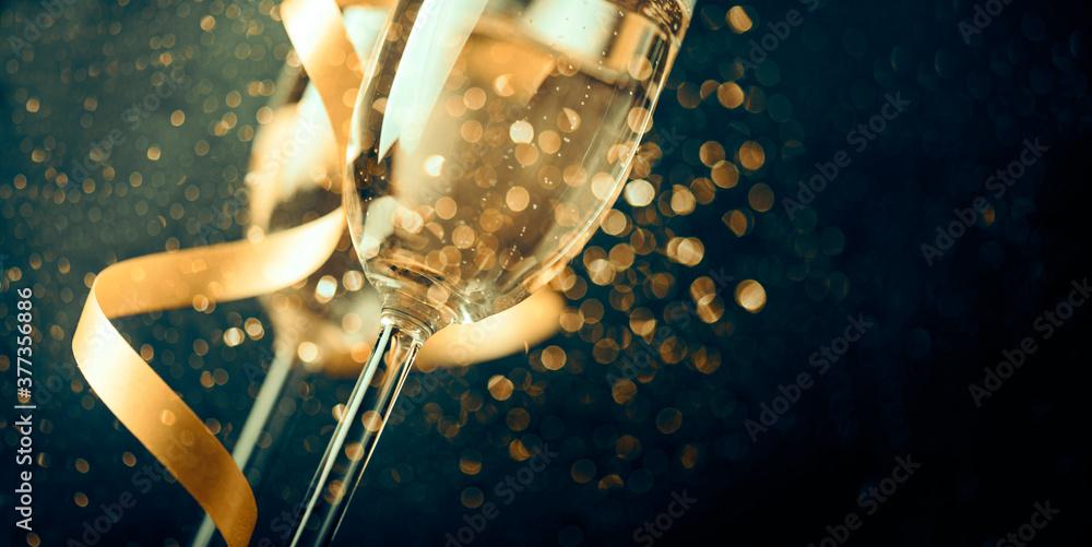 Fototapeta Two champagne glasses with golden ribbon and gold glitter splash bokeh on dark background. Luxury restaurant dinner celebration. Classy christmas and new year holiday panoramic design banner.