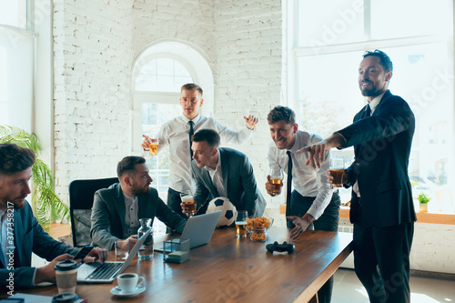 Watching football, drinking beer, cheering. Happy carefree colleagues having fun in office while their co-workers working hard and highly concentrated. Concept of fun, resting, professional occupation