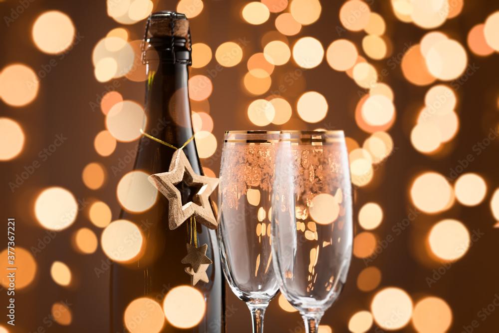 Fototapeta Festive Champagne bottle and two glasses. Fragment. Golden color and garlands.