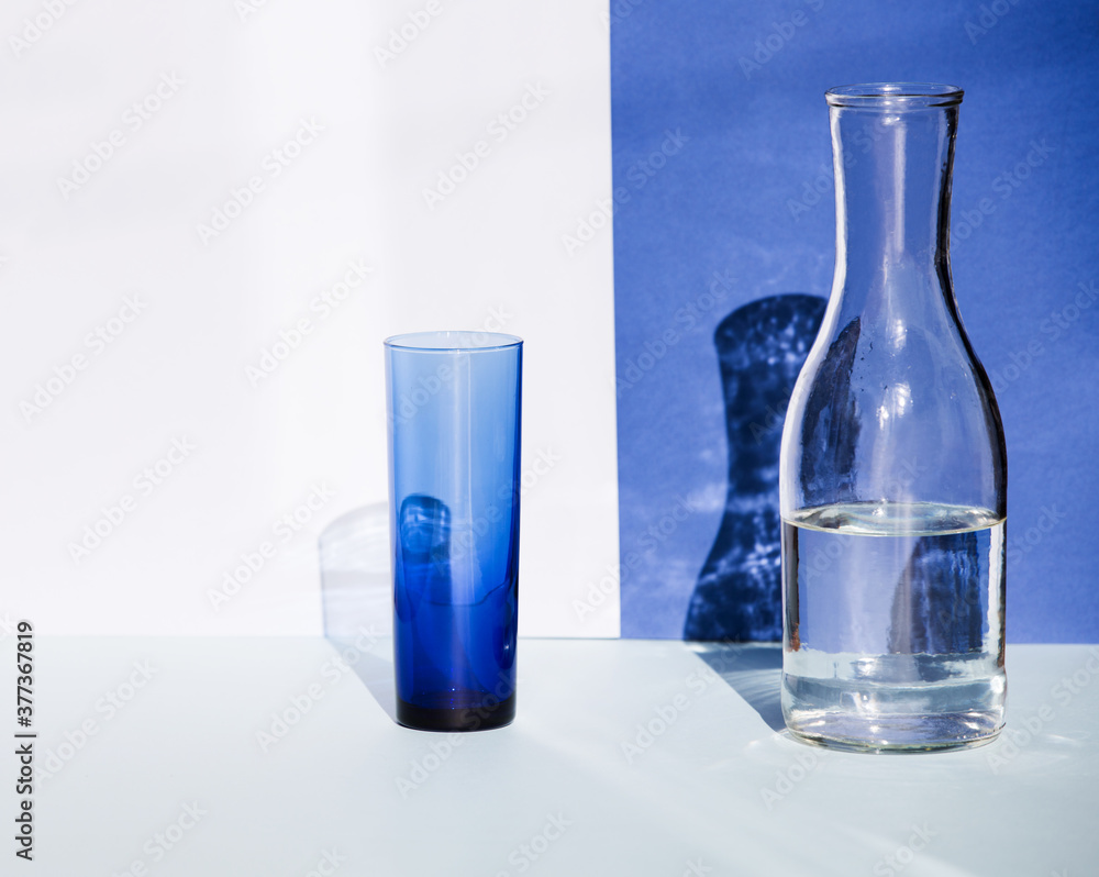 Fototapeta Transparent blue glass and water bottle in sunlight. Beautiful shadows fall on the background.