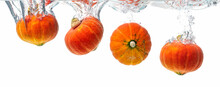 Four Orange Pumpkins Splashing Into Crystal Clear Water. Product Isolated On White Background.
