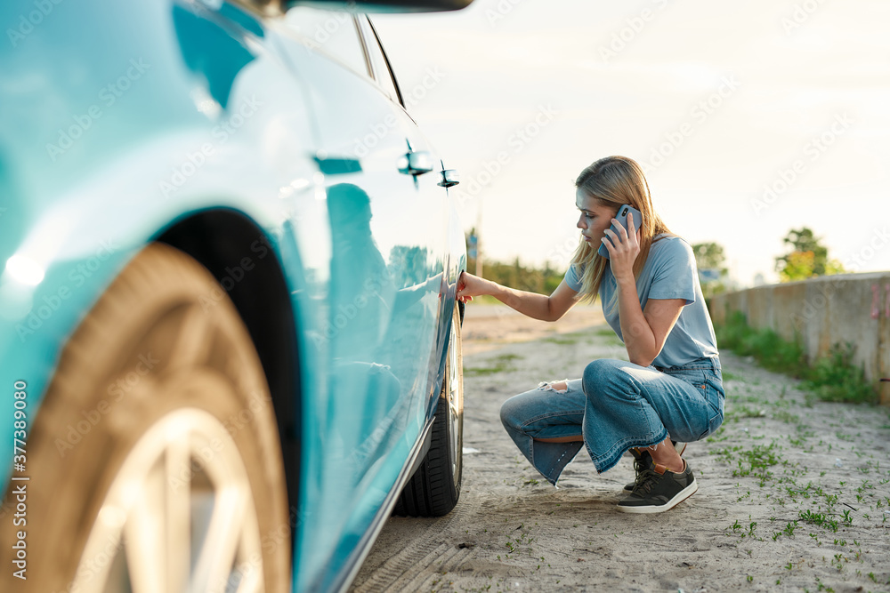 Fototapeta Attractive young woman looking sad, calling car service, assistance or tow truck while having troubles with her auto, checking wheel after car breakdown on local road side
