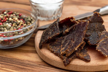 Beef Jerky With Salt And Pepper On Cutting Board. Dried Meat With Spices.