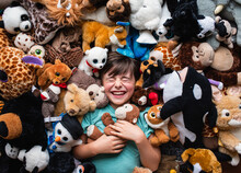 Happy Young Boy Surrounded By His Stuffed Animals Shot From Above.