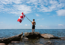 Boy Holding Canada Flag In The...