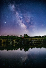 Milkyway Stars In The Night Sky Above Castle Reflecting In Water.