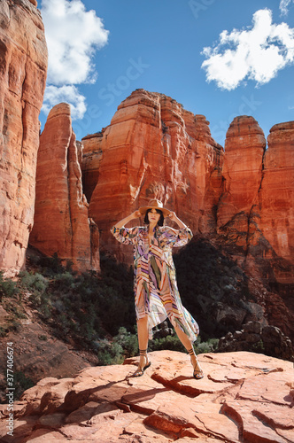 Stylish Cowgirl in dress stands in front of rock formation.