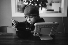 Boy Eats His Oatmeal While Wat...