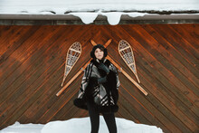 Stylish Woman Stands In Front Of Decorative Wood Wall With Snowshoes And Wooden Skis.