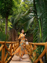 Stylish Woman In Dress On Path In Tropical Forest.