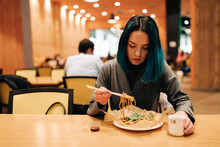 Young Woman Eating Chinese Food