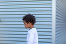 Young Child Walking In Front Of Corrugated Iron Wall