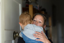 Woman Holding Child Who Opening Front Door