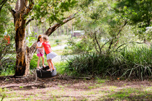 Two Little Girls Playing On A Tyre Swing On A Gum Tree In The Front Yard Of A Rural Property