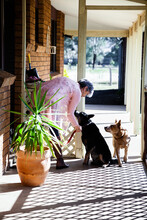 Country Woman On Verandah With Her Two Doge
