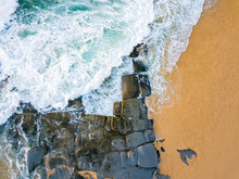 Looking Down On Waves Crashing Over Rocks On A Beach