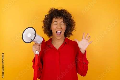 Vászonkép Emotive Young arab woman with curly hair wearing red shirt holding a megaphone  laughs loudly, hears funny joke or story, raises palms with satisfaction, being overjoyed, amused by friend