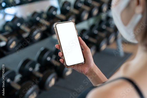 Obraz na plátně Image of woman wearing face mask and her hand holding mobile phone with white screen mockup at gym