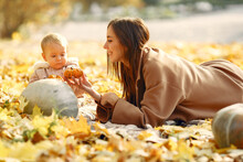 Fashionable Mother With Daughter. Family In A Autumn Park. Woman In A Brown Coat.