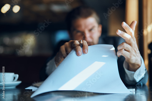 Fotografie, Obraz business man sitting at a table in a cafe documents work official coffee cup