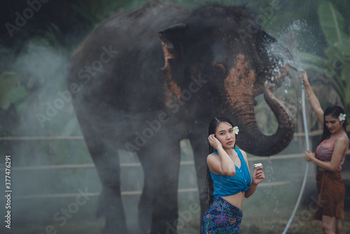 Vászonkép Asian elephants and beautiful women in Thai national costumes play in Songkran water with elephants in Thailand