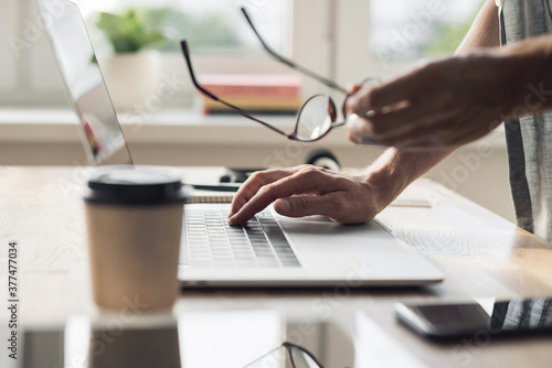 Man hands typing on computer keyboard closeup, businessman or student using laptop at home, online learning, internet marketing, working from home, office workplace, freelance concept