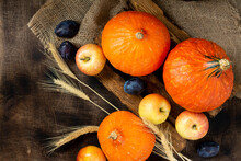Hokkaido Pumpkins, Apples And Plums Are Laid Out On The Table. The Concept Of The Fall Harvest. Thanksgiving Day. The View From The Top. Top View With Space For Text. Autumn Background