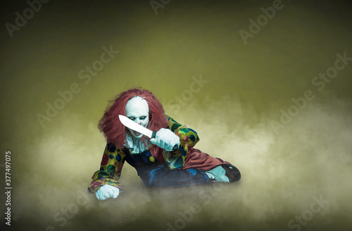 Photo scary clown with knife on a abstract background