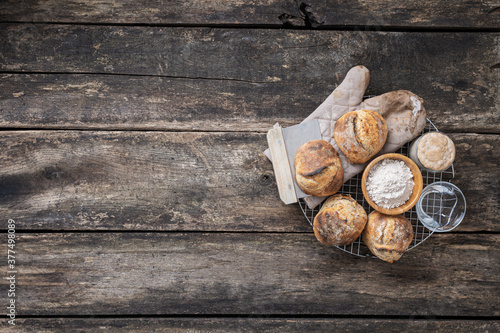 Fototapeta Freshly baked sourdough bread buns, water, flour and starter yeast placed on a round cooling rake obraz