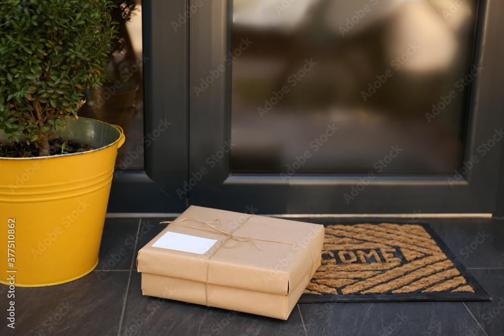 Fototapeta Delivered parcel on door mat near entrance