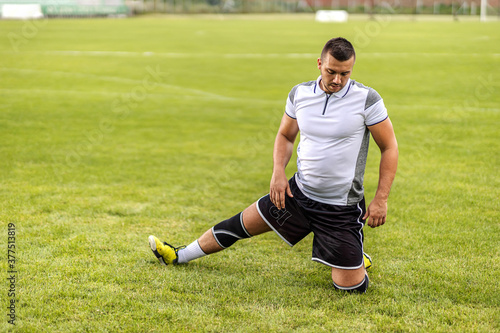 Fotografia, Obraz Dedicated attractive unshaven soccer player stretching his leg while kneeling on the field