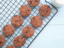 Top View Homemade Double Chocolate Chip Cookies On A Wire Rack With Glass Milk On A Blue Wooden Background. Fresh From The Oven, Copy Space...
