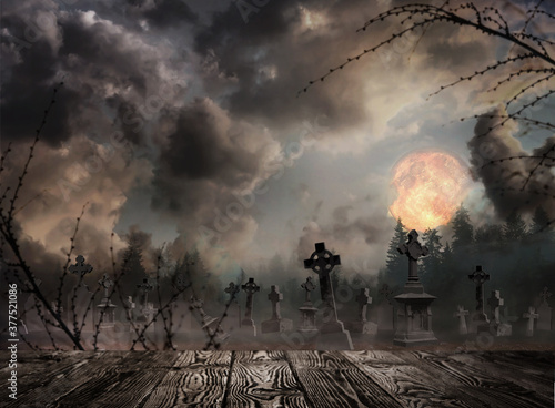 Photo Wooden surface and misty graveyard with old creepy headstones under full moon on