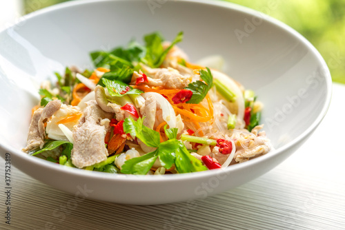 Fototapeta Thai food, spicy salad of cleared noodles or Yum Woon Sen in Thailand language. Close up food in white bowl on table, natural light. obraz