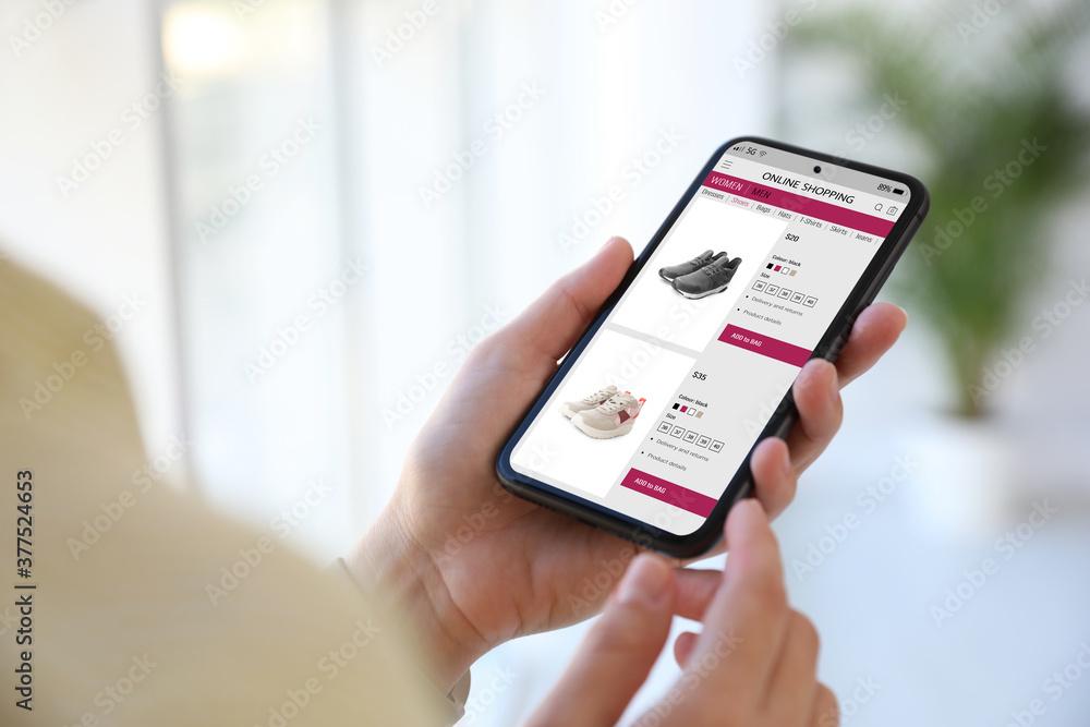 Fototapeta Woman shopping online via smartphone indoors, closeup