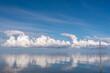 canvas print picture - Wolkenspiegelung, bei spiegelglatter Nordsee,mit Holzpfahl,im Hintergrund Windräder.