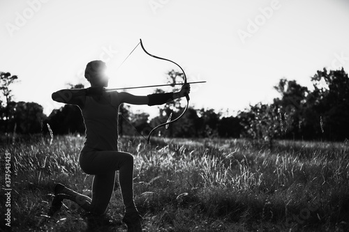 Slika na platnu Young Caucasian female archer shooting with a bow in a field at sunset
