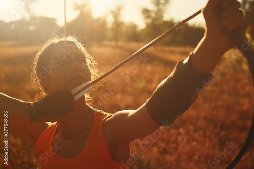 Fotografia Young Caucasian female archer shooting with a bow in a field at sunset
