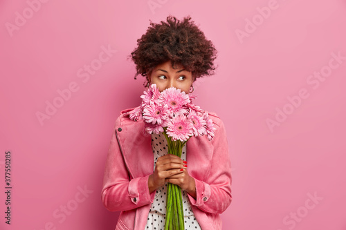Studio shot of good looking curly haired woman smells flowers, enjoys pleasant odor and stands in stylish clothes indoor Fototapet
