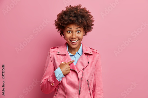Photo Happy African American woman points at herself and asks who me, wears fashionable clothes
