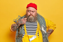 Close Up Shot Of Serious Bearded Sailor Smokes Pipe And Looks Unhappily At Camera, Poses With Fishing Net Against Yellow Studio Wall. Angry Tattooed Fisherman In Overalls Spends Free Time At Sea