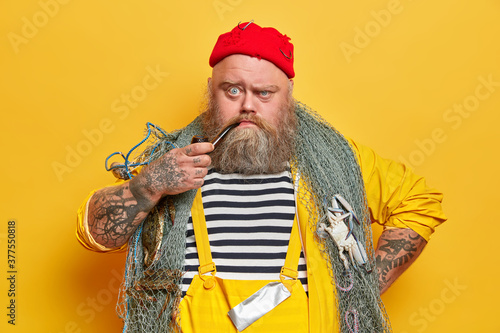 Obraz na plátně Close up shot of serious bearded sailor smokes pipe and looks unhappily at camera, poses with fishing net against yellow studio wall