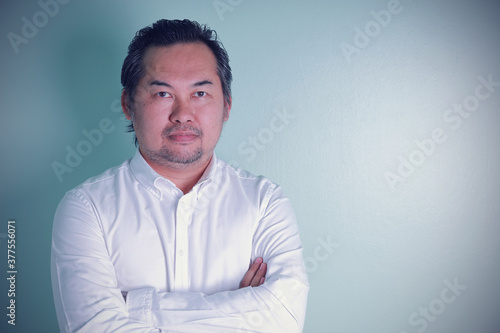 Asian businessman looks discreet standing cross arms on the green background Slika na platnu