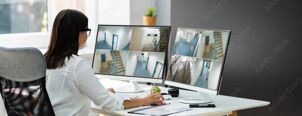 Fototapeta Businesswoman Watching CCTV Footage Of Office Interior