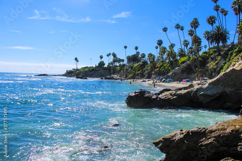 Fotografía a gorgeous view of the deep blue ocean water and the beach with people playing a